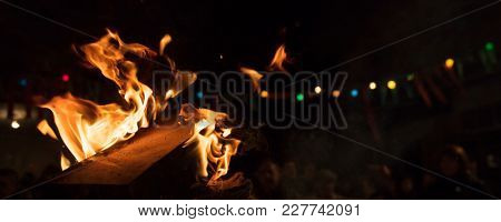 Bonfire with colorful flames and bokeh lights. Big blaze with firewoods. Blurred people on night background. Close up view with details, banner, space for text.