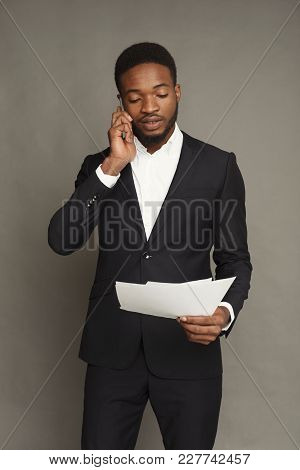 Handsome Young Black Man Portrait In Formal Wear Talking On Smartphone And Reading Documents, At Gre