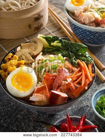 A Bowl Of Delicious Spicy Lobster Noodles With Soft Boiled Egg, Carrots, Baby Bok Choy, Mushrooms, A