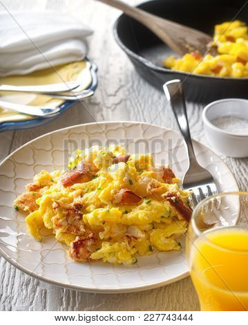 A Plate Of Delicious Lobster Scrambled Eggs With Chives.