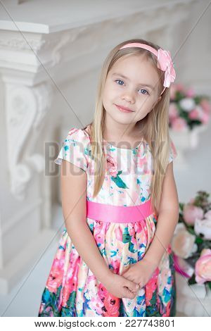 Portrait Of Little Smiling Girl Child In Colorful Dress Posing Indoor.