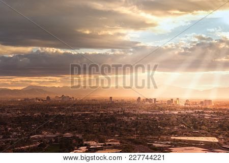 Phoenix,Az,USA; Aerial view of the downtown area, sun rays peaking through clouds.