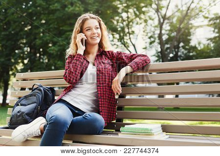 Beautiful Smiling Female Sitting And Talking On The Phone On The Bench Outdoors. Technology, Communi