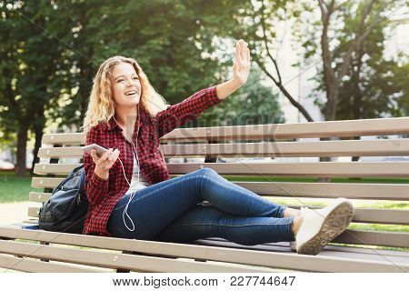 Beautiful Smiling Female Sitting And Listening To Music With Pleasure On The Smartphone On The Bench