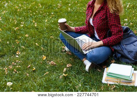 Young Casual Woman With Laptop Outdoors. Female Student Preparing For Exams With Computer, Books And