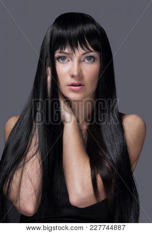 Woman with beautiful long black hair, posing in studio