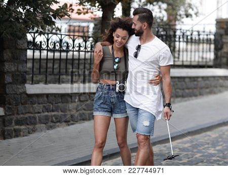 Cheerful young couple walking on urban street