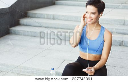 Woman Choose Music To Listen In Her Mobile Phone During Workout In City, Having Rest, Sitting On Sta