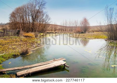 Spring Landscape, River With A Wooden Bridge,  Fine Day