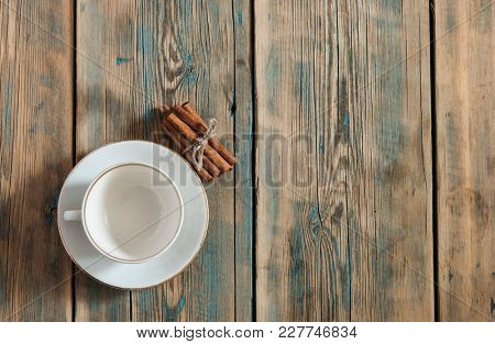 Empty white cup with saucer on a wooden background, top view