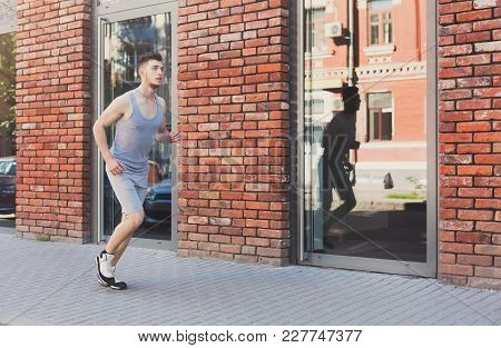 Young Man Running In City Near Brick Building With Mirror Windows, Copy Space