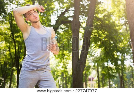 Tired Runner Sweating, Taking Run Break In Park. Athlete Man Touching His Forehead And Holding Bottl