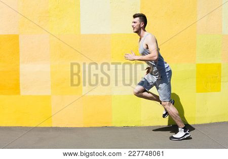 Side View Of Male Athlete Running Against Bright Yellow Graffiti Wall, Copy Space