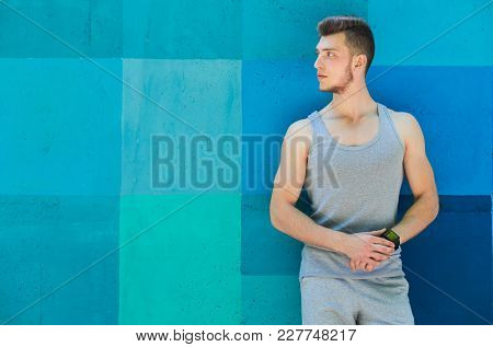 Young Sporty Man Using Smart Watch, Standing At Bright Blue Graffiti Wall Background, Copy Space. Mo
