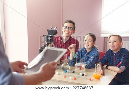 Teenagers Listening To Teacher Talking About Chemistry In Laboratory, Sitting With Reagents And Micr