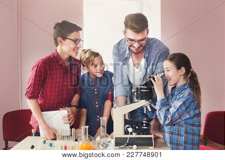 Teenagers With Teacher Making Chemical Experiment In Laboratory With Reagents And Looking Through A