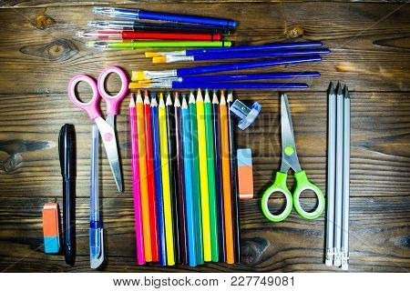 Set Of School Stationery Supplies. Colored Pencils, Pens, Scissors, Eraser, Paint Brushes On Wooden