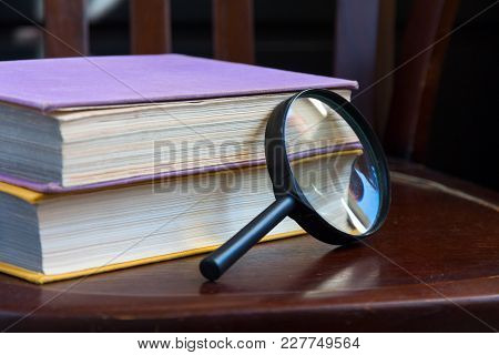 Two Closed Book And A Magnifying Glass On A Brown Wooden Chair
