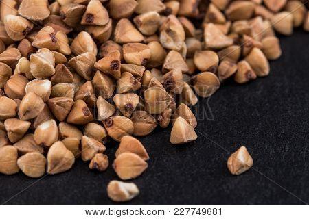 Buckwheat Groats On Black Background. Pile Of Buckwheat Groats Close Up.