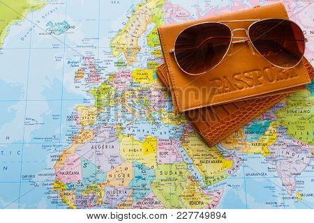 Summer Vacation Planning Background. Preparing Tourist Stuff For A Trip. Passport And Sunglasses On