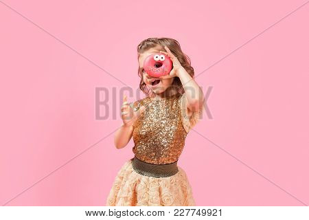 Cute Little Girl In Glittering Golden Dress Looking Through Hole In Donut With Eyes On Pink Backgrou