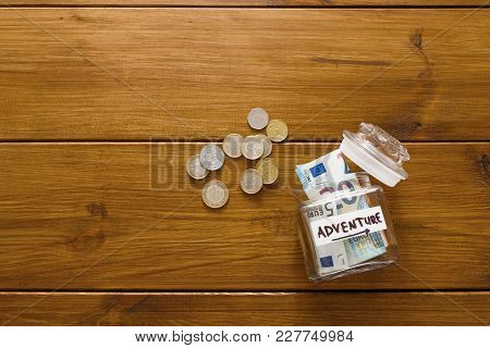 Travel Budget Concept. Money Saved For Vacation In Glass Jar On Wooden Background, Copy Space, Top V