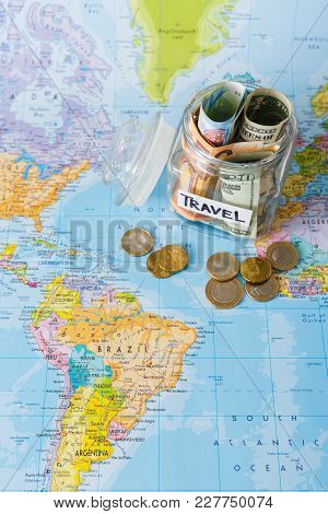 Travel Budget Concept. Money Saved For Vacation In Glass Jar On World Map Background, Top View. Bank
