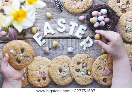 Easter Concept Background Child Holding Easter Cookies And Easter Eggs On A Wooden Background From A