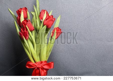Gifts For Loved Ones. A Bouquet Of Red Tulips Stands In A Glass Vase, Tied With Scarlet Ribbon.