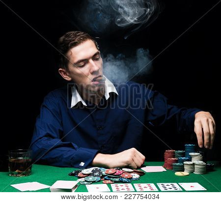 Man Is Playing Poker. Smoke Cigar And Drink Whiskey, Man Throws Chips On Table, Winning All The Chip
