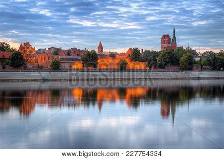 Torun old town over Vistula river at sunset, Poland
