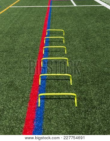 Six Yellow Mini Banana Hurdles Are Lined Up In A Staight Line On A Green Turf Field For Speed And Ag