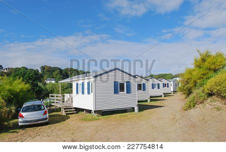 Side View White Caravan Or Mobile Home In Europe Install In Area Near Hill With Car And Parking, Bac