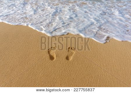 Foot Prints In The Sand And Sea Surf. Vacation Concept