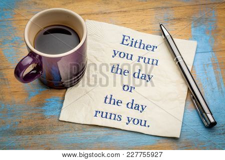 Either you run the day or  the day runs you - handwriting on a napkin with a cup of espresso coffee