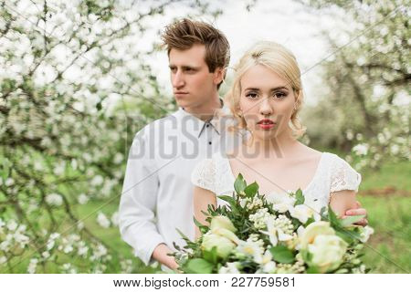 Portrait Of The Bride And Groom In The Apple Orchard. Young Beautiful Blonde Woman In Blooming Garde