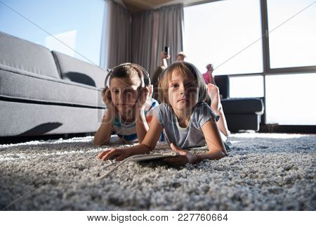 Happy Young Family Playing Together at home.kids using tablet on the floor