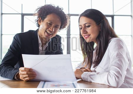 Cheerful Multi-ethnic Businessman Showing Document With Analytics To Coworker. Business Partners Ana