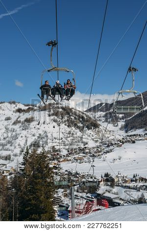 Chairlift At Italian Ski Area On Snow Covered Alps And Pine Trees During The Winter - Winter Sports