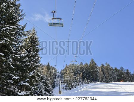 Chairlift At Italian Ski Area On Snow Covered Alps And Pine Trees