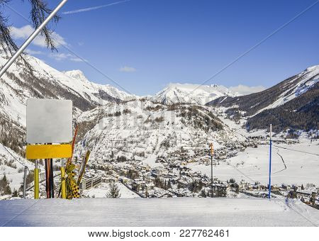 Blank Signpost At A Ski Piste Overlooking The Town Of Thuile In Italian Alps