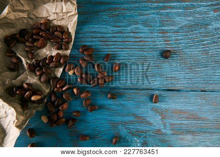 Pine Nuts On Blue Wooden Table Background, Close-up. Raw Cedar Nuts, Top View
