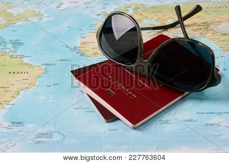 Two Passports Travel Documents And Sunglasses On The Map Of The World, Holidays Abroad. Worldwide Tr