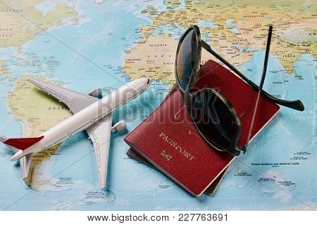 Airplane With Two Passports Travel Documents And Sunglasses On The Map Of The World, Holidays Abroad