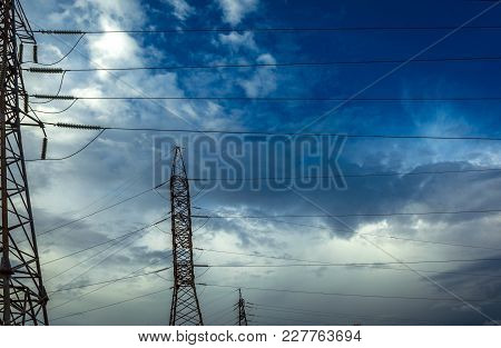 High-voltage  Power Lines At Storm Clouds. Electricity Distribution Station. High Voltage Electric T