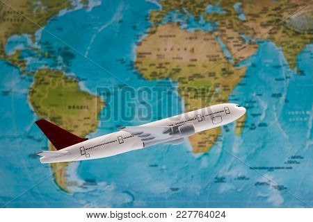Traveling, Tourism, International Flights With Flying Airplane Model And Worldmap, Close-up. White T