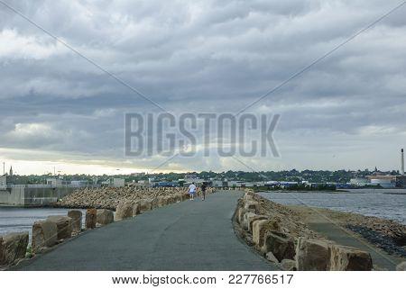 Fairhaven, Massachusetts, Usa - June 22, 2007: Two Men Walk Hurricane Barrier At Fort Phoenix As Sto
