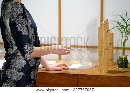 Masseuse Puts A Fragrant Oil On The Table. The Girl Is Preparing A Work Place In The Spa For The Rec