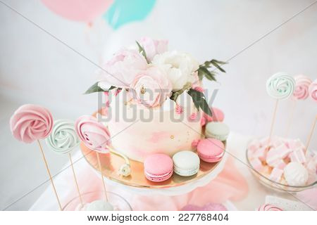 Pink Cake With Fresh Flowers. White Wedding Cake. Colored Cupcakes And Macaroni.