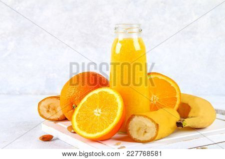 Orange Smoothies From Orange, Banana On A Gray Concrete Table
